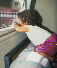 Child near flaking lead paint on windowsill